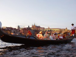 Venetian gondola with passengers wearing masks | gondolier