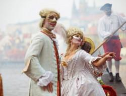 Pasažéři pravé benátské gondoly v maskách | Gondolier